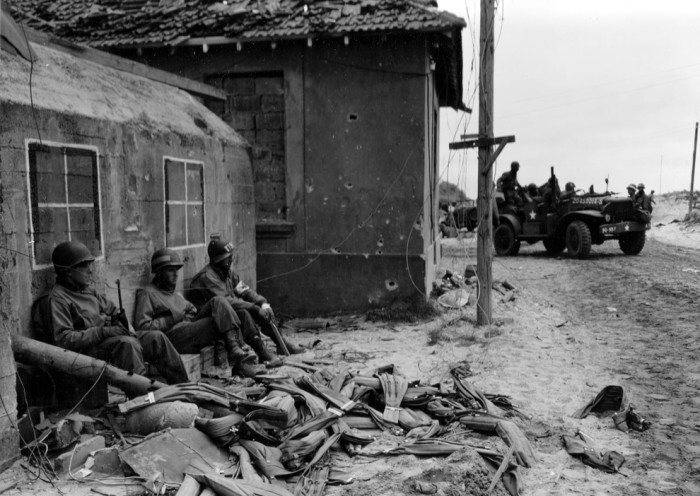 U.S. soldiers take a rest at the foot of a bunker which the Germans have painted and camouflaged to look like a house